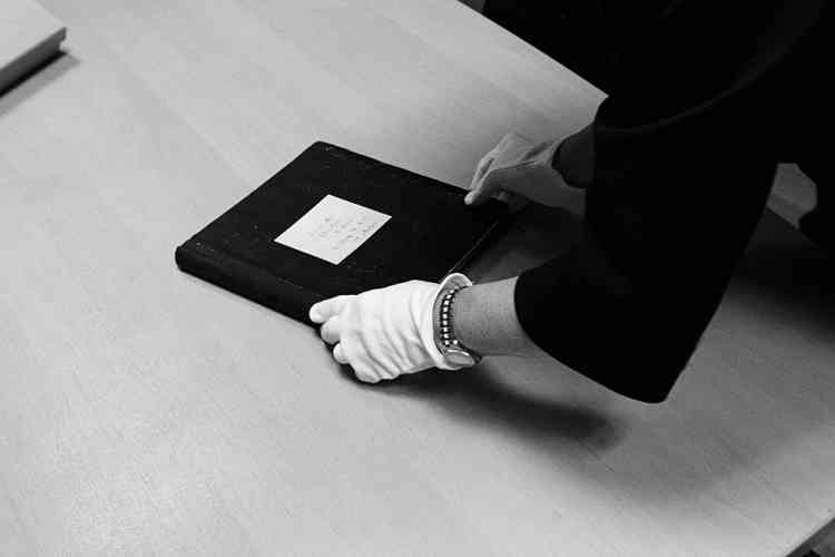 """""""J'ai trouvé les archives Dior fascinantes.  Elles sont une source d'inspiration inépuisable. J'ai cherché quelles étaient les expressions stylistiques et les attitudes que je trouvais pertinentes et modernes aujourd'hui encore. Il y a de nombreux codes typiques de M. Dior qu'on retrouve en  filigrane à travers toute la collection.""""Ci-contre et  ci-dessus,  une responsable des archives  de la maison  avec un cahier  de fabrication. Photo : Dior couture"""