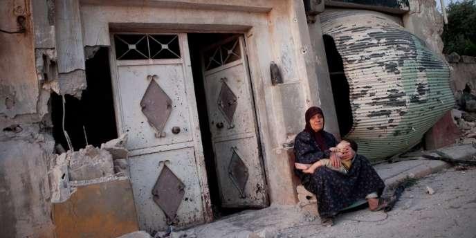 Une habitante de Treimsa assise avec son petit-fils devant une maison ravagée de l'artère pricnipale de Treimsa, dans la province centrale de Hama, où plus de 150 personnes ont été tuées jeudi.