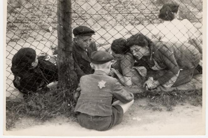 Un enfant désigné pour la déportation fait ses adieux à sa famille à travers la clôture de la prison centrale pendant la
