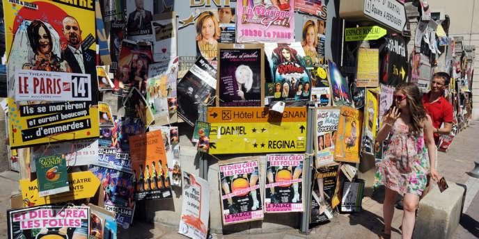 Un mur couvert d'affiches annonçant les spectacles du Festival