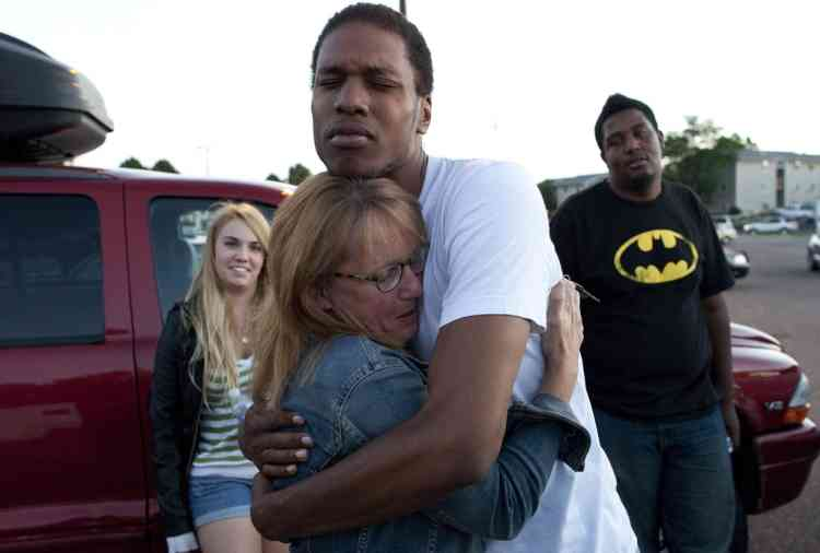 """Judy Goos, second from left, hugs her daughters friend,  Isaiah Bow, 20, while eye witnesses Emma Goos, 19, left, and Terrell Wallin, 20, right, gather outside Gateway High School where witness were brought for questioning Friday, July 20, 2012 in Denver.   A gunman wearing a gas mask set off an unknown gas and fired into a crowded movie theater at a midnight opening of the Batman movie """"The Dark Knight Rises,"""" killing at least 12 people and injuring at least 50 others, authorities said. (AP Photo/Barry Gutierrez)"""