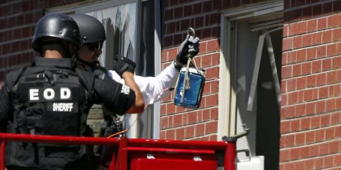 Des policiers vêtus de casques et de gilets pare-balles tentent de désamorcer l'arsenal d'explosifs dans l'appartement du tireur.
