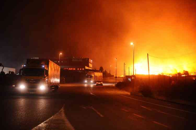 Trucks and a car ride as fire rages close to the road, on July 23, 2012, next to Figueras. Fire had been brought under control on the morning, but the main roads in the area, the A9 motorway and the D900, remain closed after a wildfire whipped up by strong winds in northeast Spain has left three people dead and more than 20 injured, trapping thousands of residents indoors. AFP PHOTO/REMY GABALDA