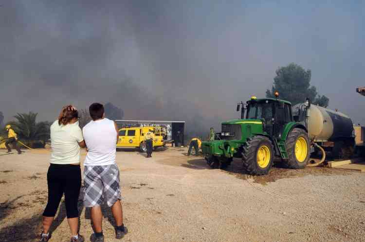 Unhabitants look on as firemen arrive to fight fire close to a farm in Avinyonet de Puigventos near Figueras, on July 23, 2012. Fire had been brought under control in some areas on the morning, but the main roads in the area, the A9 motorway and the D900, remain closed after a wildfire whipped up by strong winds in northeast Spain has left three people dead and more than 20 injured, trapping thousands of residents indoors. AFP PHOTO/REMY GABALDA