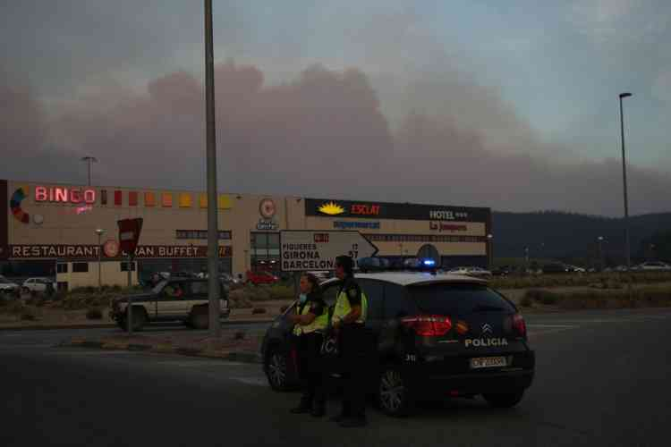 Flames are seen on July 22, 2012 close to La Junquera, near the Spanish-French border, as policemen block the road. Three people were killed as winds whipped up a wildfire that raged out of control in northeastern Spain, forcing thousands of people to take refuge indoors, officials said. The blaze broke out just after noon near the town of La Jonquera, just across the border with France and has so far destroyed about 7,000 hectares (17,000 acres) of land,  AFP PHOTO RAYMOND ROIG