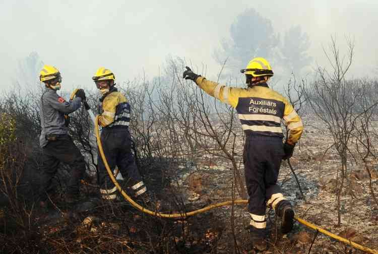Firemen fight fire in Avinyonet de Puigventos village near Figueras, on July 23, 2012. Fire had been brought under control in some areas on the morning, but the main roads in the area, the A9 motorway and the D900, remain closed after a wildfire whipped up by strong winds in northeast Spain has left three people dead and more than 20 injured, trapping thousands of residents indoors. AFP PHOTO/REMY GABALDA