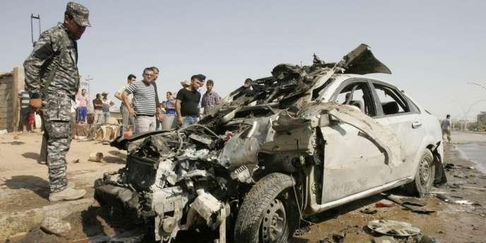 Un policier s'approche d'une carcasse de voiture après une explosion à Kirkouk au nord de Bagdad.
