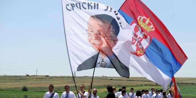 Des Serbes brandissent deux drapeaux, un aux couleurs de la Serbie et un autre à l'effigie de l'un des chefs de file ultranationaliste du pays, Vojislav Seselj, près de Pristina, le 28 juin.