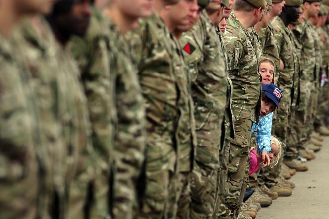 Des enfants attendent le passage du caporal Johnson Beharry, porteur de la flamme olympique, héros britannique de la guerre en Irak.