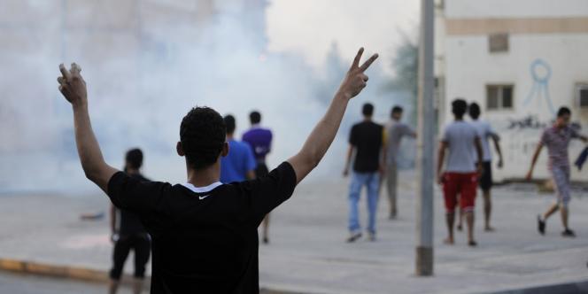 Un manifestant fait le signe de la victoire alors que la police anti-émeute tire des gaz lacrymogènes dans un village à l'ouest de Manama, le 20 juillet.