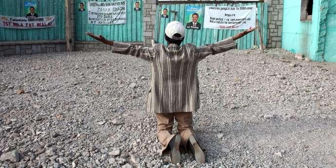 Une personne malgache prie à l'emplacement d'un ancien supermarché qui appartenait à l'ex-président Marc Ravalomanana, avant d'être détruit en 2009.