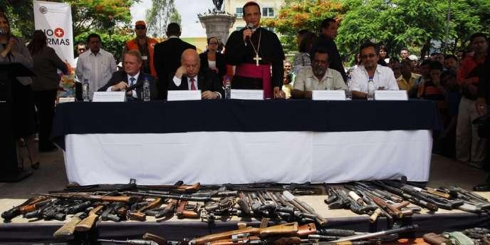 L'évêque Fabio Colindres, aumônier de l'armée salvadorienne, a négocié une trêve entre le Mara Salvatrucha et Barrio 18, deux gangs du Salvador. Il se tient ici devant les armes remises par les deux bandes.