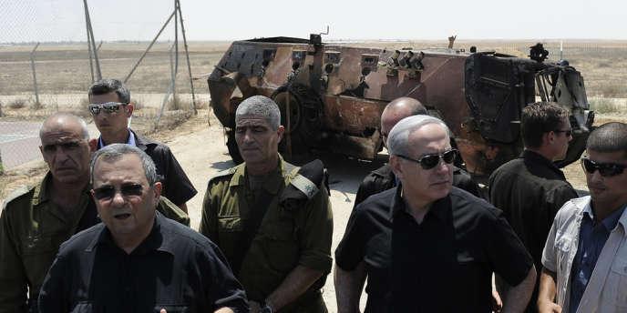 Ehoud Barak (à gauche) et Benyamin Nétanyahou, sur le lieu où a été détruit le blindé volé par des terroristes, près du poste de Karm Abou Salem, le 6 août.