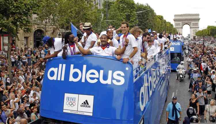 France's Olympic champions and medallists ride on an open-air bus as fans gather on the Champs-Elysees near the Arc de Triomphe in Paris as they return home after the London 2012 Olympic Games August 13, 2012.  REUTERS/Benoit Tessier   (FRANCE - Tags: SPORT OLYMPICS)