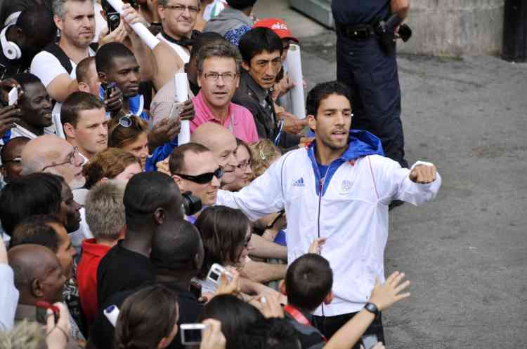 French athlete and silver medalist Mahiedine Mekhissi-Benabbad meets supporters on the Champs-Elysees avenue as French athletes celebrate on top of a double decker bus during the French Olympic Team victory parade in Paris, on August 13, 2012. France finished the London Olympics Games with 34 medals including 11 gold, 11 silver and 12 bronze, and placed on the seventh position in the all nations ranking. AFP PHOTO / MEHDI FEDOUACH
