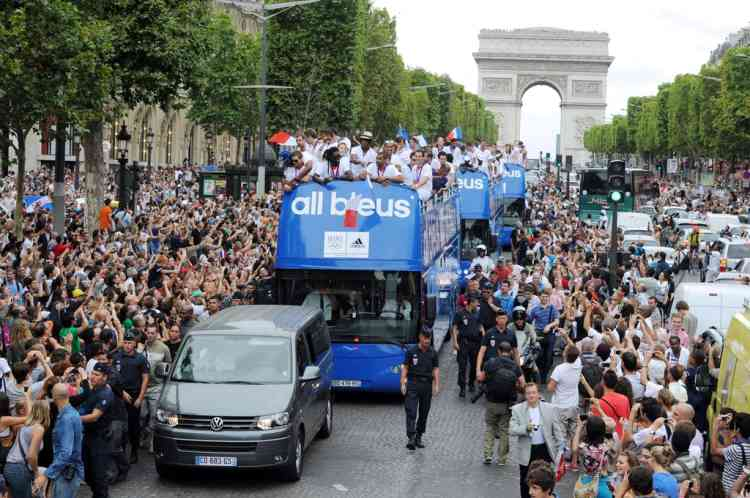 French athletes celebrate on top of a double decker bus surrounded by supporters during the French Olympic Team victory parade on the Champs-Elysees avenue in Paris, on August 13, 2012. France finished the London Olympics Games with 34 medals including 11 gold, 11 silver and 12 bronze, and placed on the seventh position in the all nations ranking. AFP PHOTO / MEHDI FEDOUACH