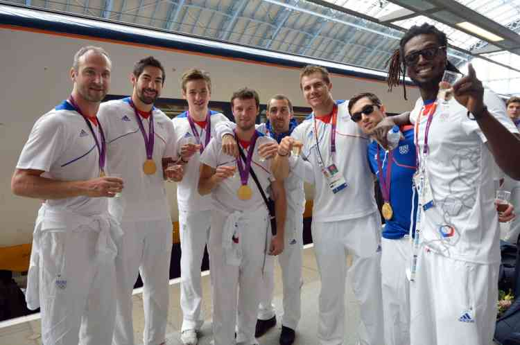 French Handbal gold medalist team drink a glass of champagne prior to take a train back to Paris at St Pancras railway station after the London 2012 Olympic Games on August 13, 2012 in London. France finished the London Olympics Games with 34 medals including 11 gold, 11 silver and 12 bronze, and placed on the seventh position in the all nations ranking. AFP PHOTO / ERIC FEFERBERG