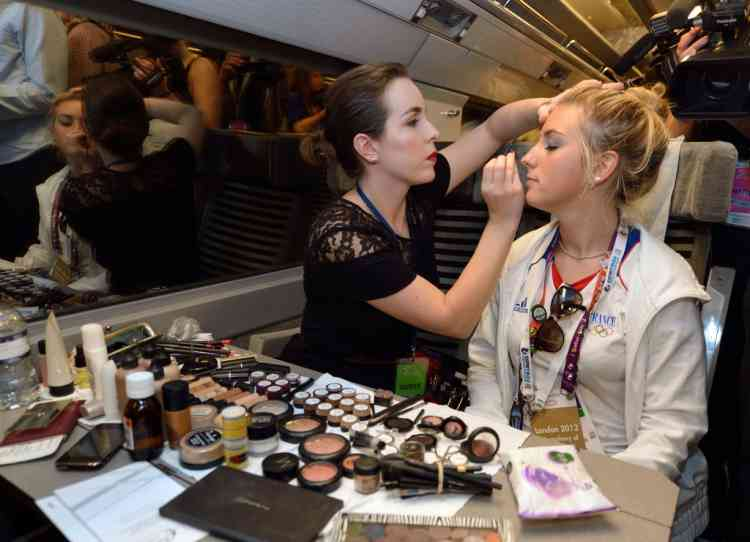French cycliste Pauline Ferrand Prevot (L) have a make up in the train going back to Paris after the London 2012 Olympic Games on August 13, 2012 in London. France finished the London Olympics Games with 34 medals including 11 gold, 11 silver and 12 bronze, and placed on the seventh position in the all nations ranking. AFP PHOTO / ERIC FEFERBERG