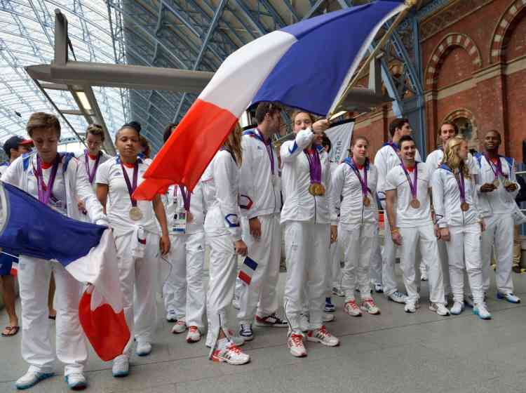 French swimmer Camille Muffat (C) waves the french flag as french medalists pose for a family picture at St Pancras railway station before leaving London after the London 2012 Olympic Games on August 13, 2012 in London. France finished the London Olympics Games with 34 medals including 11 gold, 11 silver and 12 bronze, and placed on the seventh position in the all nations ranking. AFP PHOTO / ERIC FEFERBERG