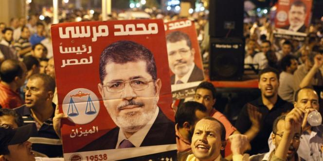 Des Egyptiens devant le palais présidentiel du Caire, supportent la décision du Frère musulman, Mohamed Morsi, de limoger le maréchal Hussein Tantaoui et plusieurs hauts responsables militaires, le 12 août.