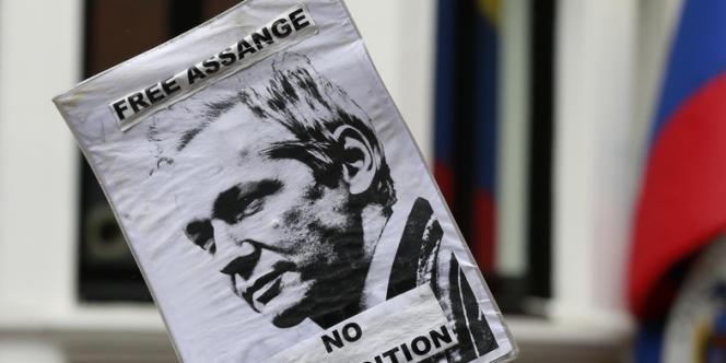 Un manifestant brandit une pancarte pour demander la suspension de l'extradition de Julian Assange.