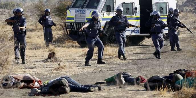 Des policiers devant des corps allongés de mineurs, devant la mine de Marikana, le 16 août.