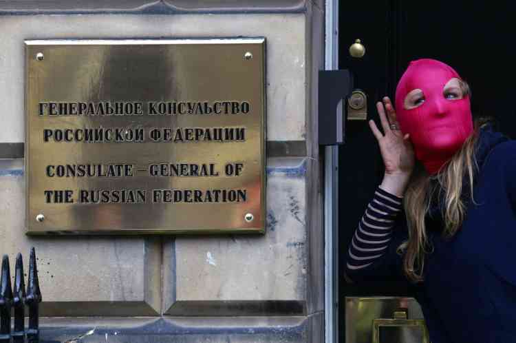 A protestor gestures next to a sign outside the Russian Consulate General building during a demonstration of support for the female Russian female punk band Pussy Riot in Edinburgh, Scotland August 17, 2012. A Russian judge found three women from the punk band Pussy Riot guilty of hooliganism motivated by religious hatred on Friday for staging an anti-Kremlin protest on the altar of Moscow's main Russian Orthodox church.  REUTERS/David Moir (BRITAIN - Tags: ENTERTAINMENT POLITICS CRIME LAW)