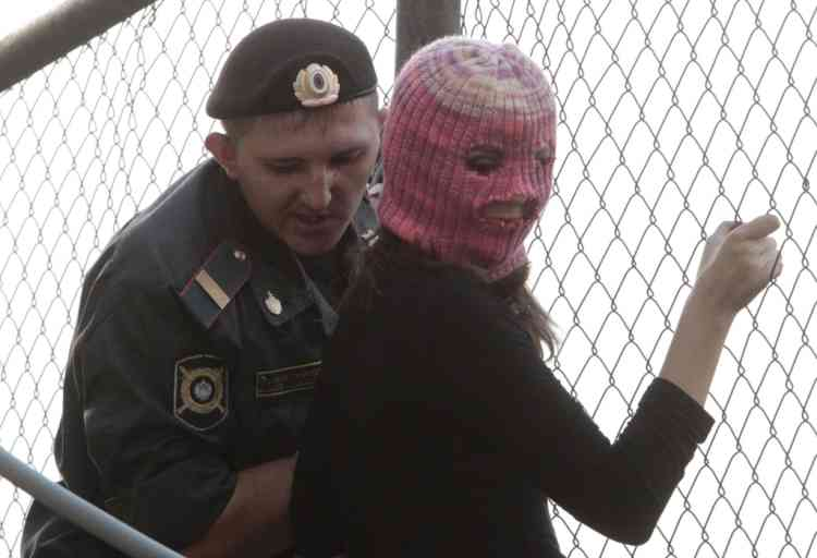 "A policeman detains a supporter of the female punk band ""Pussy Riot"" while climbing a fence enclosing the Turkish embassy near a court building in Moscow, August 17, 2012. A judge sentenced three women who staged an anti-Kremlin protest on the altar of Moscow's main Russian Orthodox church to two years in jail on Friday in a trial seen as test of President Vladimir Putin's tolerance of dissent.   REUTERS/Sergei Karpukhin (RUSSIA - Tags: CRIME LAW POLITICS CIVIL UNREST)"