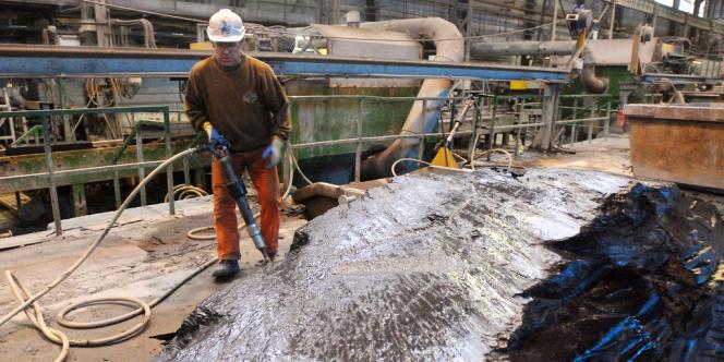 Un ouvrier découpe des blocs de schiste, le 05 décembre 2007, après leur extraction dans les ardoisières d'Angers à Trélazé.