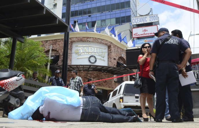 Le corps d'un homme tué par balles, entouré par la police fédérale, sur l'avenue touristique  La Costera, qui longe la baie d'Acapulco, le 17 août .