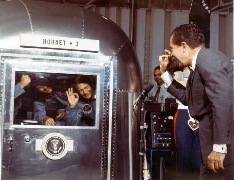 """President Richard M. Nixon and the Apollo 11 astronauts exchange """"A-OK signs"""" through the window of the Mobile Quarantine Facility 24 July 1969 aboard the USS Hornet.  The astronauts, (L-R) Neil A. Armstrong, Michael Collins and Edwin E. Aldrin Jr splashed down in the Pacific Ocean at 12:50 p.m. EDT 24 July, 900 miles southwest of Hawaii at the completion of their successful lunar landing mission. AFP PHOTO NASA"""