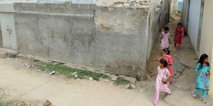 De jeunes Pakistanaises musulmanes passent devant la maison de Rimsha, la jeune fille chrétienne accusée d'avoir brûlé des versets du Coran.