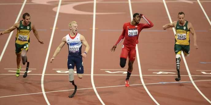 Jonnie Peacock passe la ligne d'arrivée du 100 m en premier, suivi de l'Américain Richard Browne, du Sud-Africains Arnu Fourie et d'Oscar Pistorius.