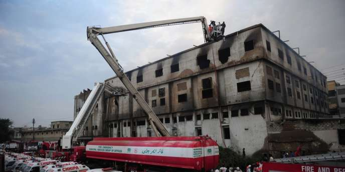 Pakistani firefighters and medical personnel take part of rescue operation in the garment factory in Karachi on September 12, 2012. At least 63 people were killed when a blaze engulfed a garment factory in Pakistan's largest city Karachi, an official said.  AFP PHOTO/Asif  HASSAN