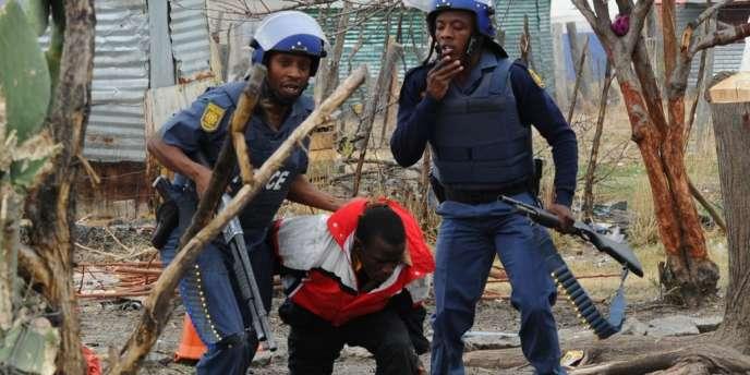 La police sud-africaine arrête un mineur de Marikana, le 15 septembre.