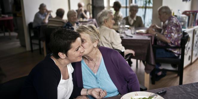Une personne âgée embrasse une animatrice pendant son repas à l'accueil de jour pour malades d'Alzheimer, le 6 Juillet 2011 au sein du village générations de Saint-Apollinaire.