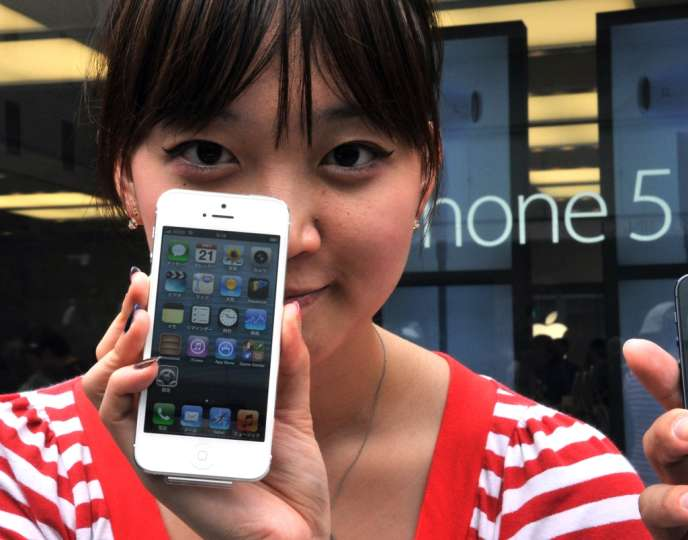 Sur le marché japonais, où il n'est plus le seul opérateur à proposer l'iPhone d'Apple, Softbank voit sa progression ralentie. En photo, une cliente et son iPhone 5, à Tokyo, le 21 septembre 2012.