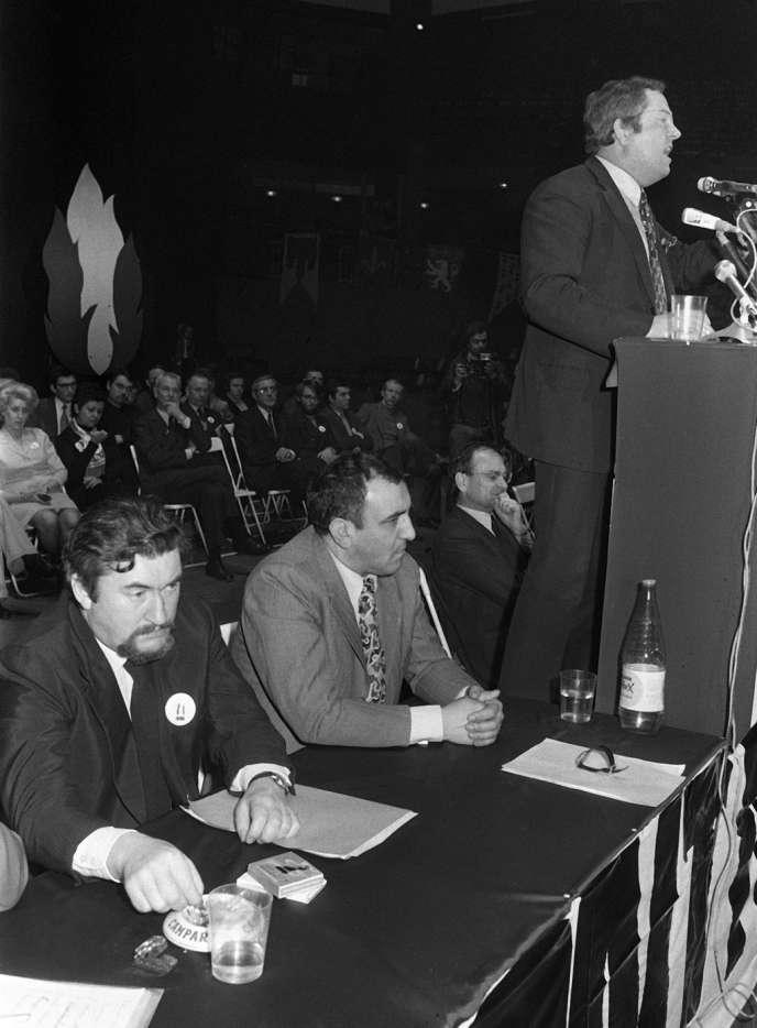 Le président du Front national Jean-Marie Le Pen prononce un discours, le 18 janvier 1973 à Paris, en présence de François Brigneau (assis à gauche) et de Roger Holeindre, quelques mois après la fondation du parti.
