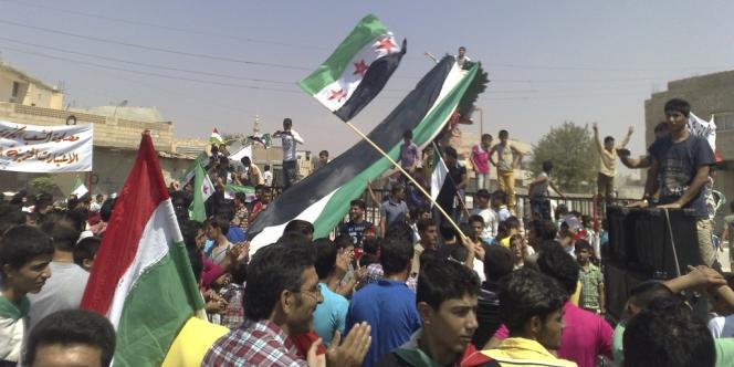 Des manifestants brandissent des drapeaux kurdes et de l'opposition syrienne, le 31 août, à Kobané, près d'Alep.