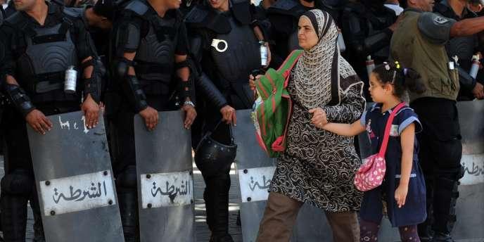 Une femme et sa fille passent devant la police à Tunis le 21 septembre.