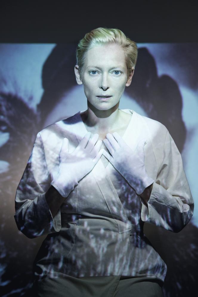 Blouse et gants blancs, visage nu, souliers chair :  Tilda Swinton  s'efface derrière  les vêtements qu'elle présente.
