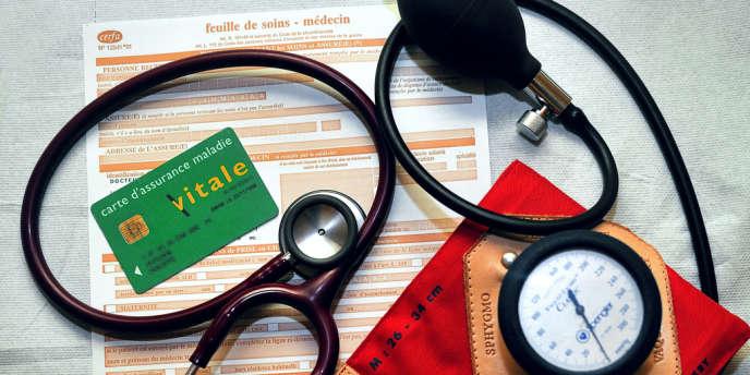 Une feuille de soins, une Carte d'assurance maladie Vitale, un stétoscope et un tensiomètre, dans un cabinet médical.