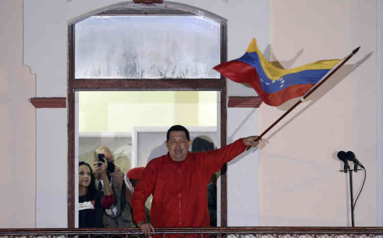 Venezuelan President Hugo Chavez waves a Venezuelan flag while speaking to supporters after receiving news of his reelection in Caracas on October 7, 2012. According to the National Electoral Council, Chavez was reelected with 54.42% of the votes, beating opposition candidate Henrique Capriles, who obtained 44.97%. AFP PHOTO/JUAN BARRETO