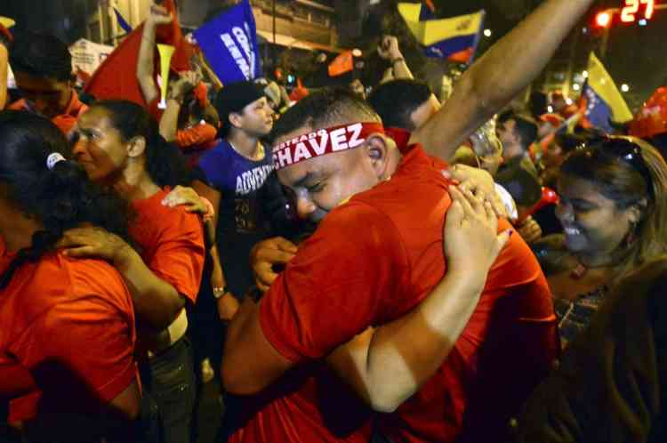 Supporters of Venezuelan President Hugo Chavez celebrate after receiving news of his reelection in Caracas on October 7, 2012. According to the National Electoral Council, Chavez was reelected with 54.42% of the votes, beating opposition candidate Henrique Capriles, who obtained 44.47%. AFP PHOTO/Luis Acosta