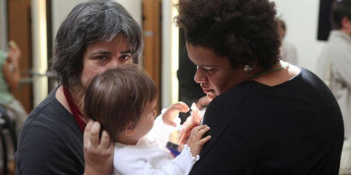 Un couple de femmes homosexuelles tiennent leur enfant, le 17 septembre 2010 à Paris lors des premières journées européennes homoparentales.
