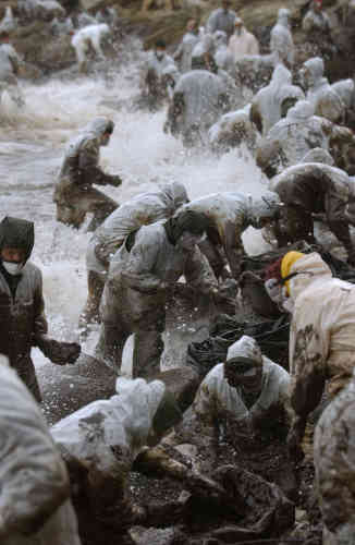 Hundreds of Spanish military and volunteers clean up oil on the Filgueras beach in Cies Island 15 December 2002, as Galacia braces for another wave of ol pollution to wash up on its beaches. AFP PHOTO CHRISTOPHE SIMON