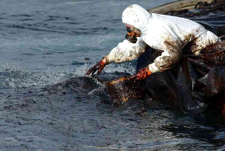 A fisherman from Cangas collects oil from the sunken tanker Prestige in front of Vigo Rias 11 December 2002.  The tanker is estimated to have spilled 10,000 tons of its 77,000-ton cargo before sinking 19 November 2002.       AFP PHOTO CHRISTOPHE SIMON