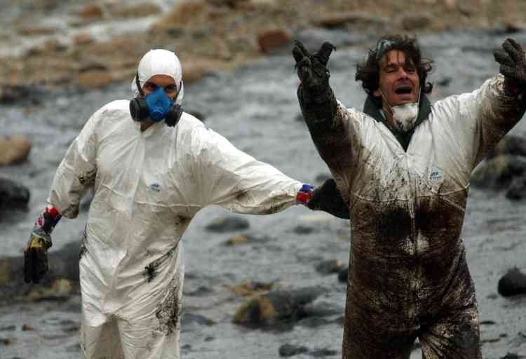 """A volunteer (R) gestures at the press 02 December 2002 before the visit of King Juan Carlos of Spain at Muxia's oil-covered beach as a new wave a petrol hit the shore 01 December 2000, leaking from the sunken petrol tanker """"Prestige"""" in the northwest of Spain.  AFP PHOTO/Pierre-Philippe MARCOU"""