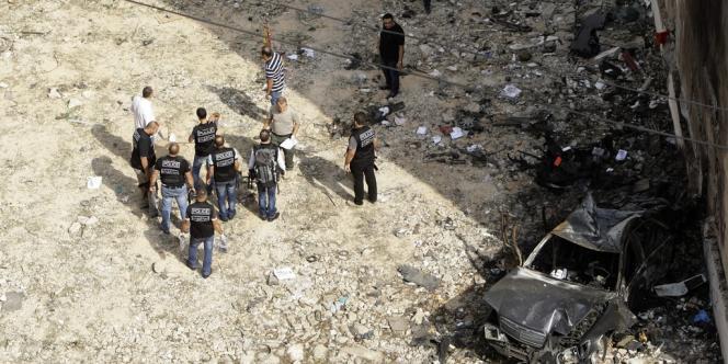 Des enquêteurs inspectent les lieux de l'attentat à la voiture piégée qui a frappé le centre de Beyrouth, vendredi.