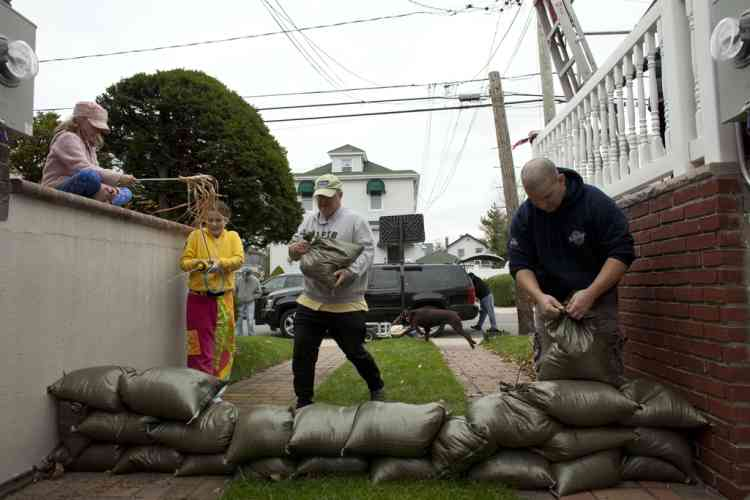 NEW YORK, NY - OCTOBER 28: Two families who live side by side install a wall of sandbags to protect their basement as Hurricane Sandy approaches on October 28, 2012 in the Rockaway Beach neighborhood of the Queens borough of New York City. New York City Mayor Michael Bloomberg announced a mandatory evacuation on low-lying coastal areas of the city. Sandy, which has already claimed over 50 lives in the Caribbean is predicted to bring heavy winds and floodwaters to the mid-Atlantic region.   Allison Joyce/Getty Images/AFP== FOR NEWSPAPERS, INTERNET, TELCOS & TELEVISION USE ONLY ==